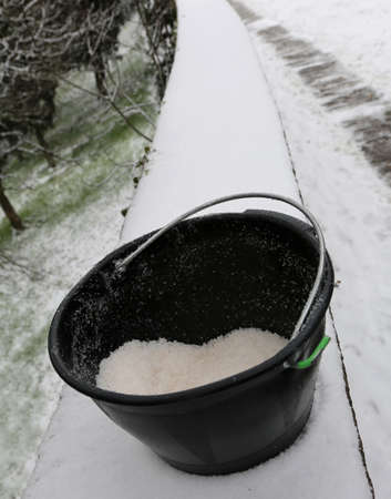 black bucket with salt used to melt ice and snow from the sidewalk after the snowfall Stock Photo