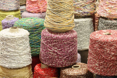 coils and spools of fine colored wool thread for the creation of handmade sweaters