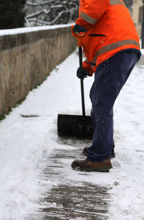 worker while shoveling snow from frozen sidewalk after snowfall in winter Stock Photo