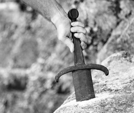 hand of the knight who extracts Excalibur the legendary sword in the stone