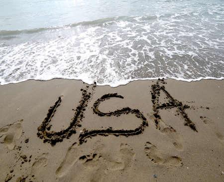 USA text written on the sand of the beach near the ocean