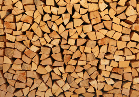 background of many stacked wooden logs in the woodshed Фото со стока