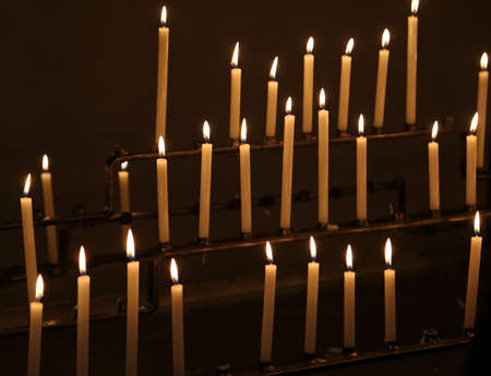 many wax candles lit for the religious ceremony by the faithful in the church