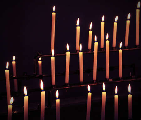 many candles with flames during religion mass Stock Photo