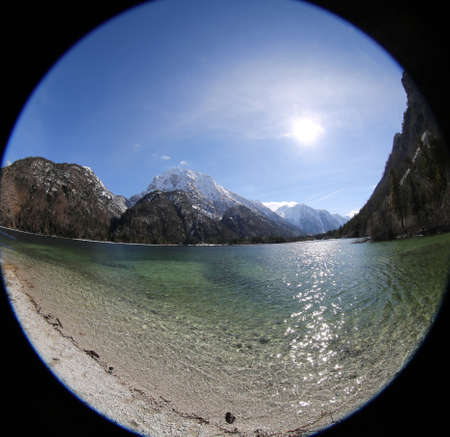 strange view like a hole by fisheye lens of alpine little lake called Predil Lake Northern Italy and the mountains with white snow