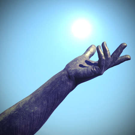 hand of statue trying to catch the white sun in the blue sky
