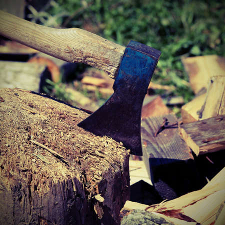 big broad ax of the woodcutter on the block of wood with vintage effect Stock Photo