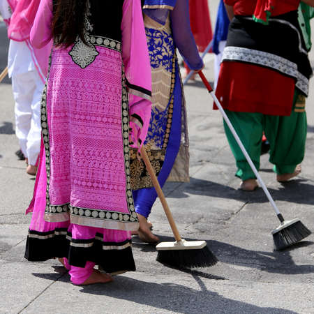 Sikh  women barefoot while scavenging the road with a broom during a Sikh festival Stock Photo