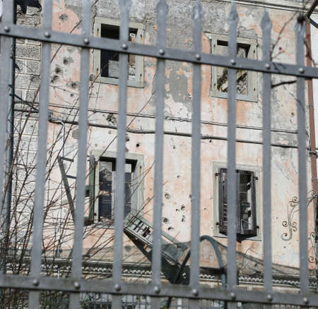 abandoned home behind a railing of iron with broken windows by war