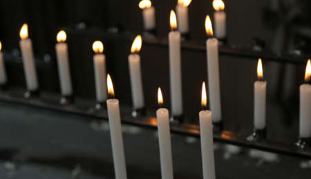 candles made with wax with flames during religion mass in the church Stock Photo
