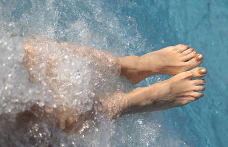 two feet of a young woman during the hydromassage session in the spa pool Stock Photo
