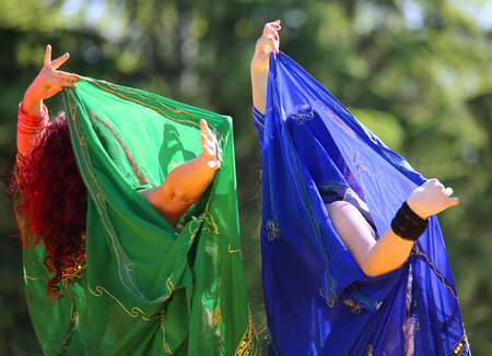 women with colorful clothes during belly dancing in outdoors