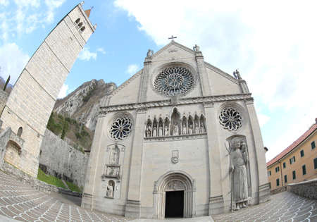 Antique facade the Cathedral of the city of Gemona with the high bell tower photographed with fisheye lens in Northern Italy. The Church was destroyed by a very strong earthquake in 1976 Editorial