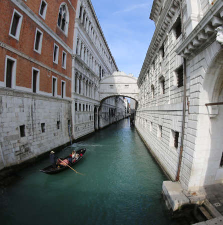 gondolier carries tourists on the gondola under the Bridge of Sighs in Venice in Italy Stock Photo