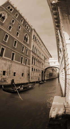 Ancient bridge of sighs and ducal palace photographed by fish eye lens and a gondola boat in Venice Italy