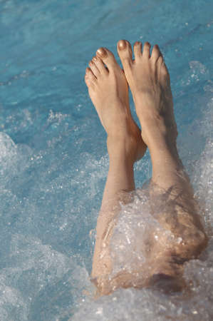 two womans feet during the hydromassage session in the spa pool