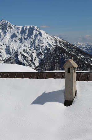 chimney of a chalet in mountains with snow