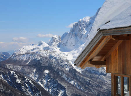 wooden chalet and mountains with snow in winter