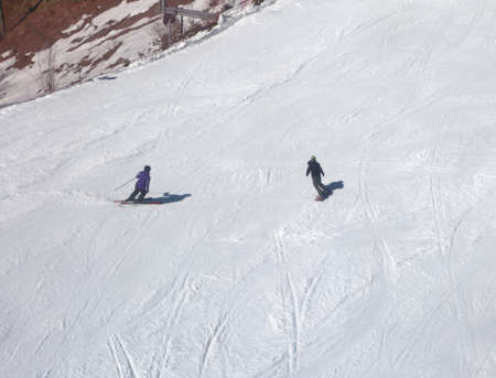 Two skiers in the slope with snow in winter
