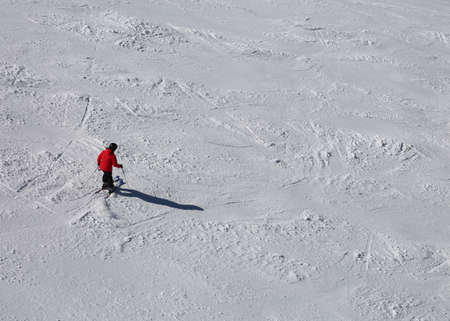 One skier in the slope with snow with red clothing in winter