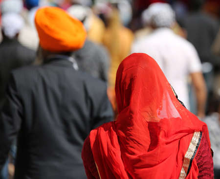 Sikh woman with flamboyant red veil and in front a man with a turban