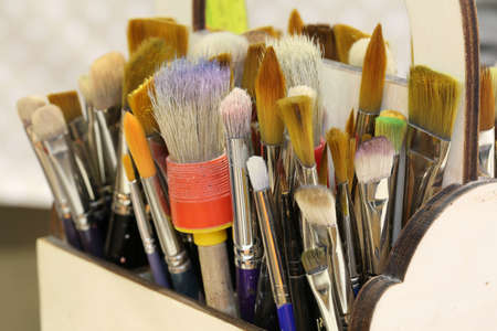 brushes of various shapes and sizes ready to be used by a painter to paint a painting