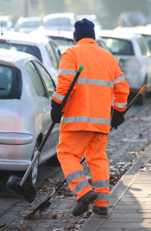 street cleaner with a recognizable orange jacket that cleans the streets of a crowded city Stock Photo