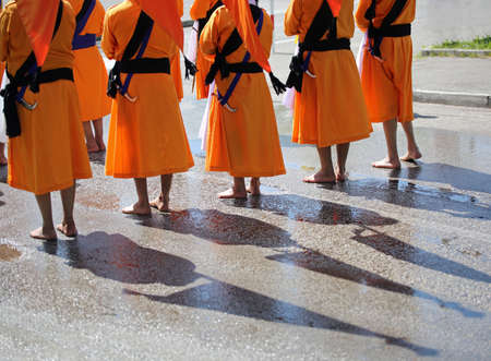 Sikh soldiers with bare feet and orange robes and with swords in their belts