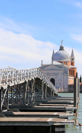 long pedestrian bridge made of boats to reach the church called MADONNA DELLA SALUTE with big dome on the island of Venice in Italy
