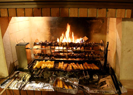 grilled birds and polenta on a fireplace during a village fair