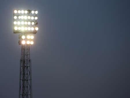 spotlights of a football stadium lit to illuminate a game played at night Stock Photo