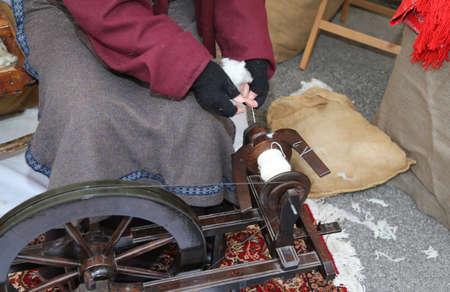 elderly woman sewing a woolen dress using an old spinning wheel