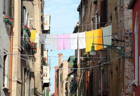 clothes hanging on a line between two houses on a street in Venice
