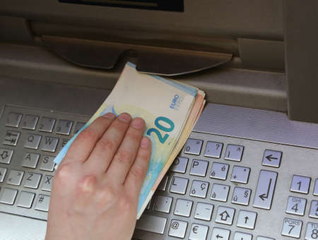 hand takes a lot of money from an ATM with euro currency and the keyboard of the electronic machine