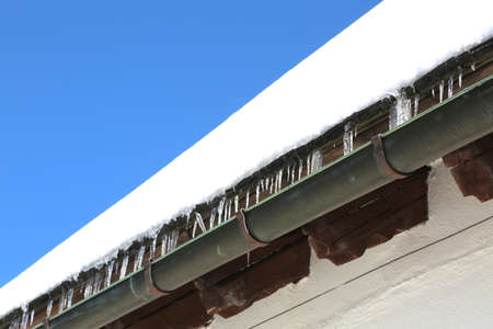 Gutter with icicles of ice on the roof after copious winter snowfall Stock Photo