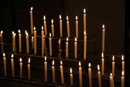many candles made with wax with flames during religion mass in the church Stock Photo