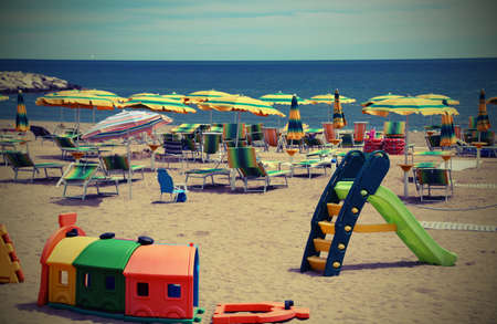 playground on the sea beach in summer with many sun umbrellas and vintage efffect Stockfoto