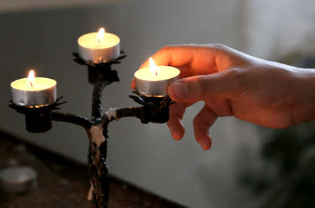 hand of young boy with candle during holy mass in the church Stock Photo