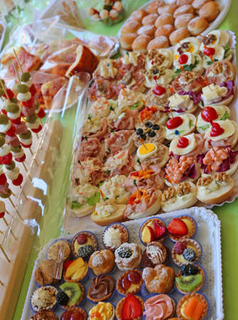 buffet with many trays overflowing with sweet pastries and sandwiches