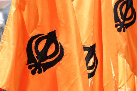 symbol of the Sikh religion called KHANDA formed by two scimitars on orange background