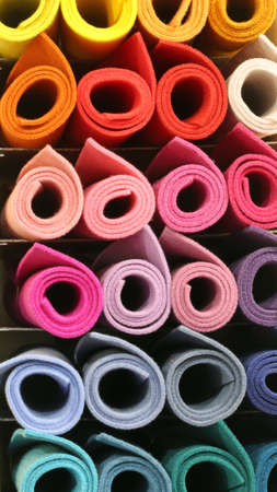 many colored big rolls of fabric in the shelf of the tailoring