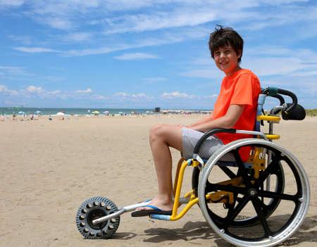 junger behinderter Junge auf Rollstuhl im Strand nahe dem Meer im Sommer Standard-Bild