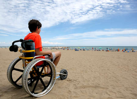 boy on the special wheelchair with aluminum alloy wheels on the beach in summer Stock Photo