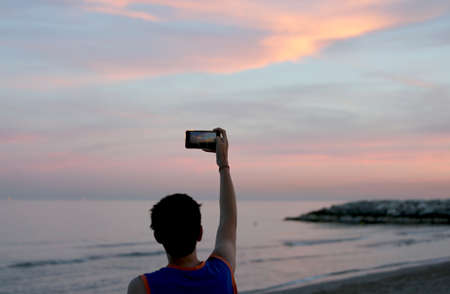 boy photographs the beautiful orange sunset by the sea with a smartphone
