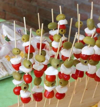 Brochettes de caprese avec olives vertes tomate mozzarella et nombreux sandwichs à la fête