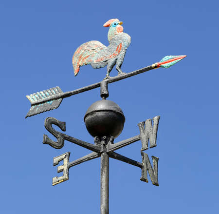 vintage weathercock on blue sky background
