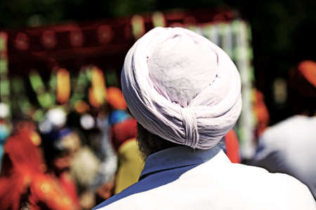 Sikh man with pink turban and long white beard during the religious rite Stock Photo