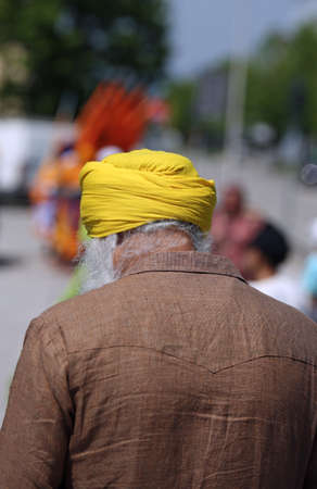 old man with yellow turban with white beard and brown jacket in the city