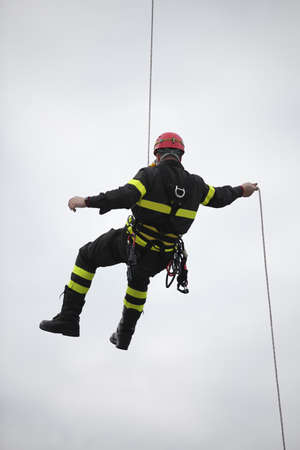 harassed fireman hanging from a cord suspended in vacuum during an exercise