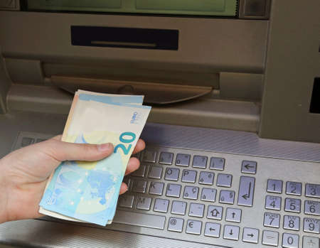 atm machine and european banknotes on the hand of boy 写真素材